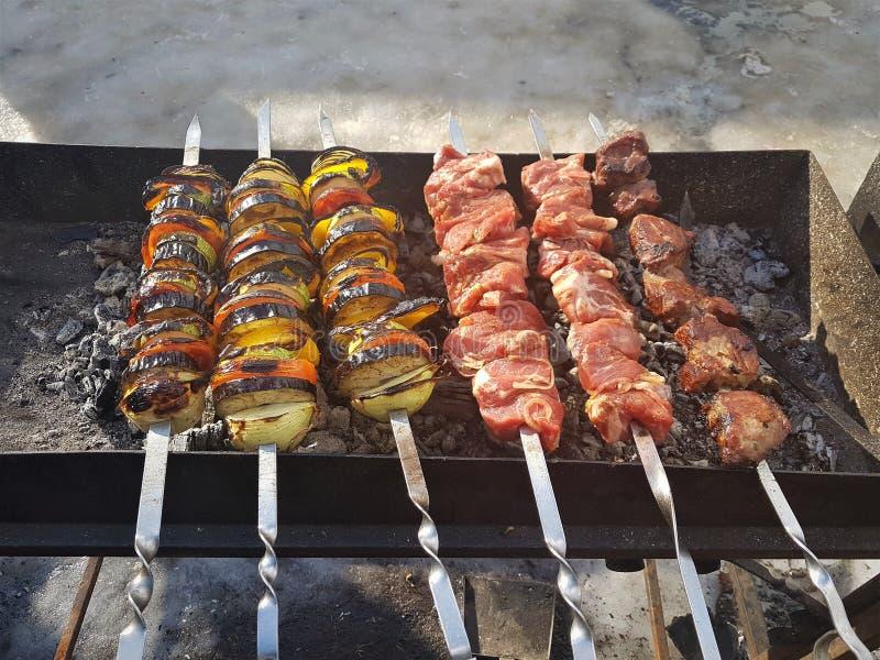 Saftiges mariniert im Gewürzfleischkebab auf Aufsteckspindeln, gekocht und auf einem Feuer- und Holzkohlengrillgrill, in Form sch lizenzfreie stockfotos