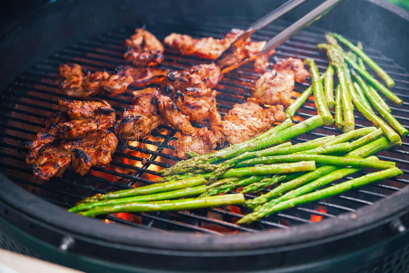 Saftiges Stück Fleisch kochend auf einem Grill mit einer Seite des Spargels Speisen des Konzeptes von Nahrung buffet Nahrung stockbild