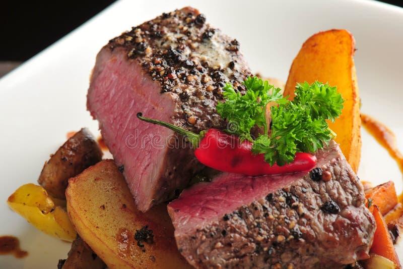 Saftiges Steak mit Ofenkartoffeln und Paprikas stockfotografie