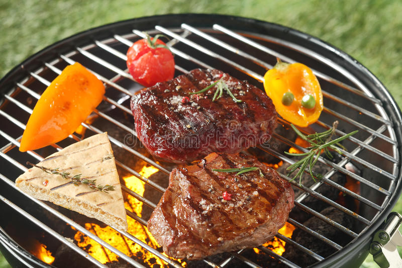 Saftiges zartes Rumpsteak, das auf einem Grill grillt lizenzfreie stockfotos