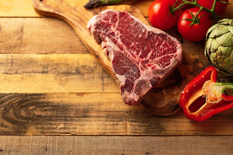 Saftigt nytt stycke av marmorerad nötköttbiff med grönsaker för att grilla Kulinarisk bakgrund, receptbok, läcker mat, biff royaltyfria bilder