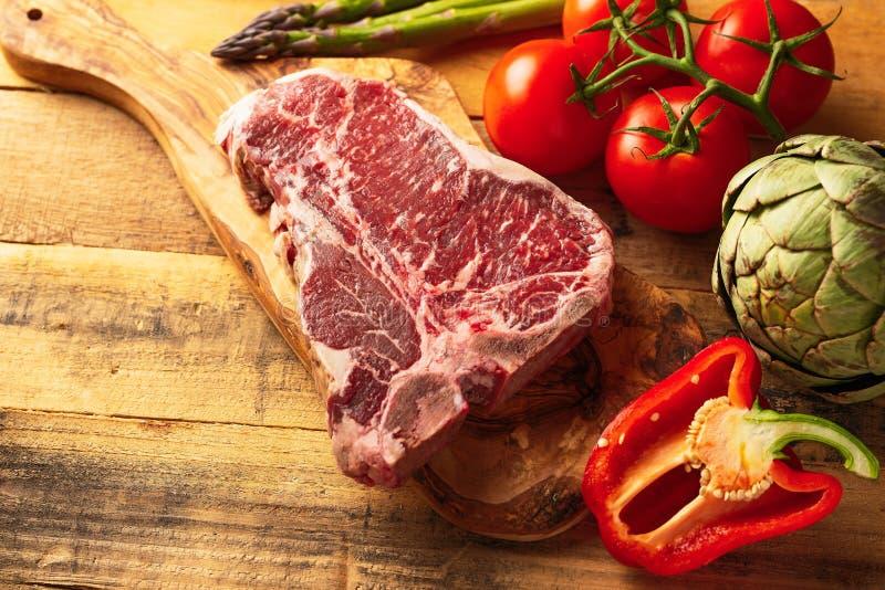 Saftigt nytt stycke av marmorerad nötköttbiff med grönsaker för att grilla Kulinarisk bakgrund, receptbok, läcker mat som lagar m royaltyfri fotografi