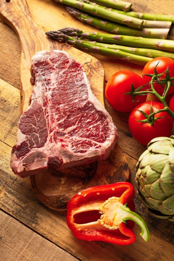 Saftigt nytt stycke av marmorerad nötköttbiff med grönsaker för att grilla Kulinarisk bakgrund, receptbok, smakmat, laga mat för  arkivfoto