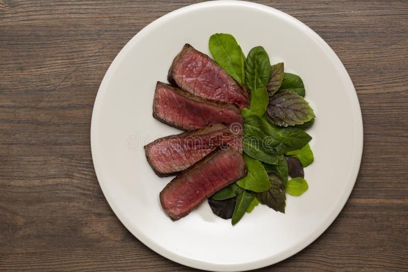 Saftigt sällsynt nötkött för biffmedel med grön sallad och tomater arkivbild