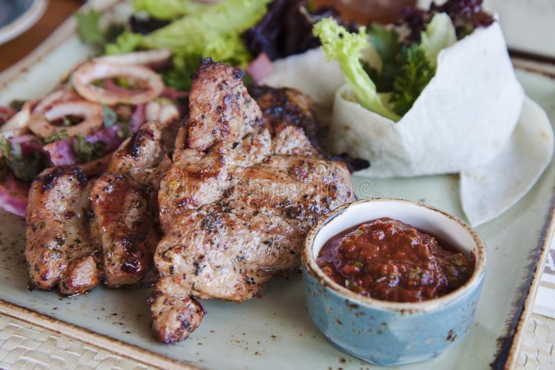 Saftigt skivat kött med sås och sallad på en platta royaltyfria foton
