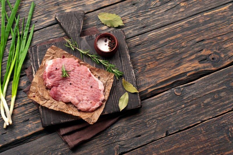 Saftigt stycke av kött, kvist av rosmarin, lök, lagerblad royaltyfri foto