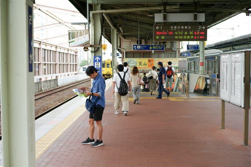 Saga, Japón: 1 de septiembre de 2016 - situación asiática del hombre del retrato y lectura del mapa en la plataforma de la estaci fotos de archivo libres de regalías