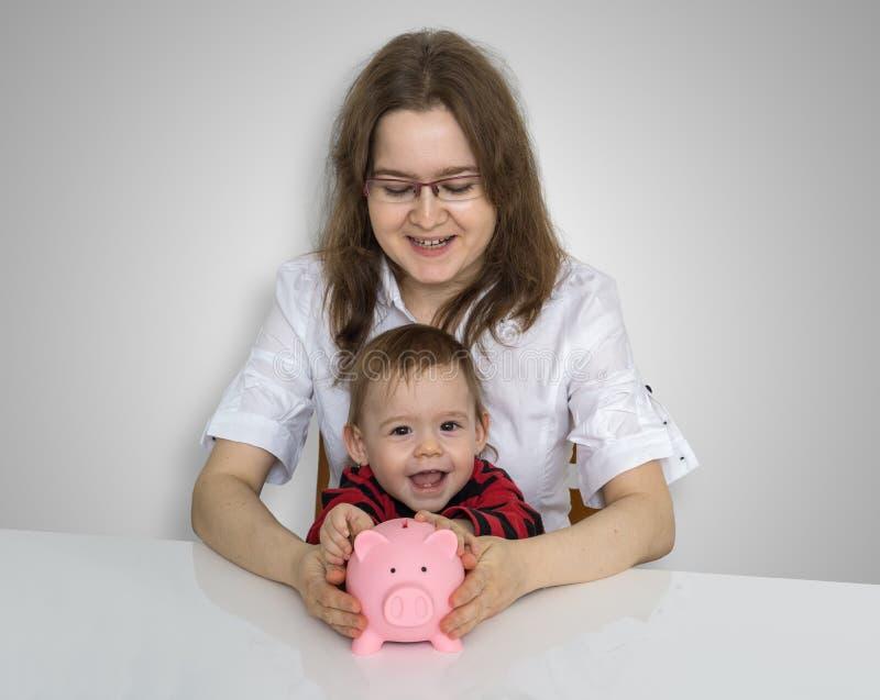 A sagacidade de mãe nova sua criança está recolhendo moedas em vagabundos leitães do dinheiro foto de stock