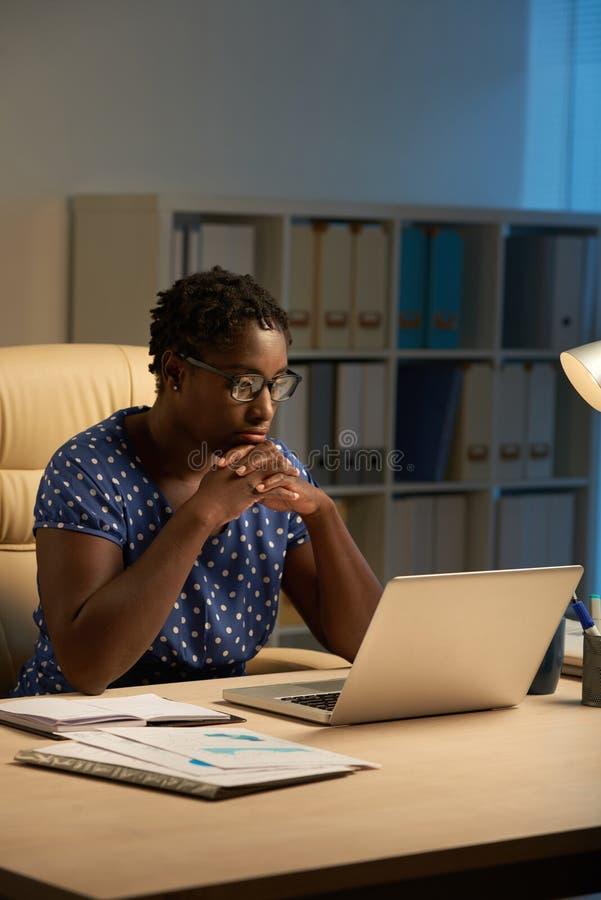 Sagacidade fêmea do empresário que trabalha na noite fotografia de stock