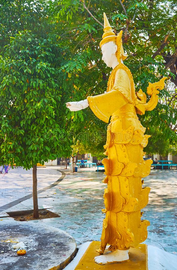The Nat statue in garden of Kaunghmudaw Pagoda, Sagaing, Myanmar. SAGAING, MYANMAR - FEBRUARY 21, 2018: The statue of Nat spirit in traditional golden attire royalty free stock photography