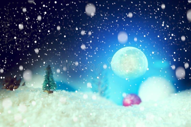Sagajulbakgrund med jul klumpa ihop sig på snö över gran-träd, natthimmel och månen grunt djupfält Elemenna arkivfoto