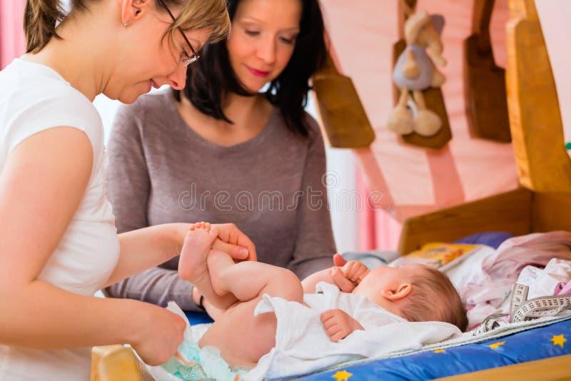 Sage-femme examinant le bébé nouveau-né images libres de droits