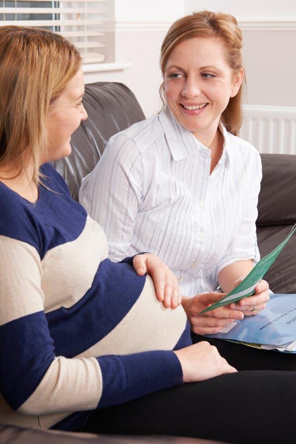 Sage-femme Making Home Visit à la femme enceinte photographie stock