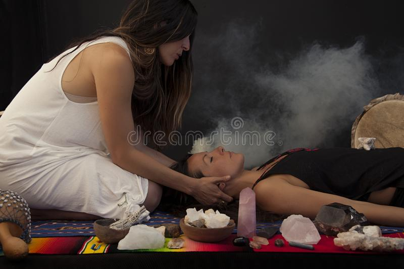 Sage Women In Crystal Ceremony. Two Women in a sacred shamanic healing ceremony with Sage Smudge, Rose Quartz, and other sacred stones royalty free stock photos