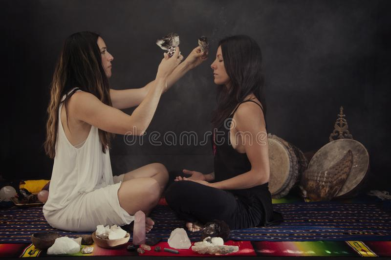 Sage Women In Crystal Ceremony. Two Women in a sacred shamanic healing ceremony with Sage Smudge, Rose Quartz, and other sacred stones royalty free stock image