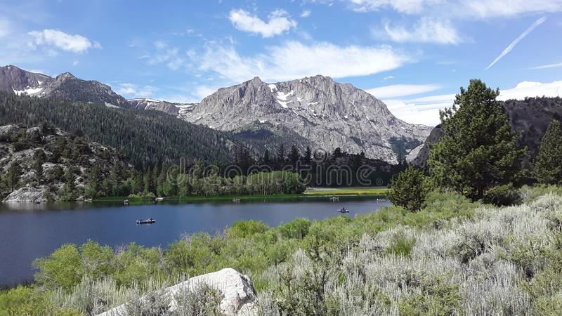 With sagebrush in the foreground a mountain and blue sky over a lake royalty free stock photos