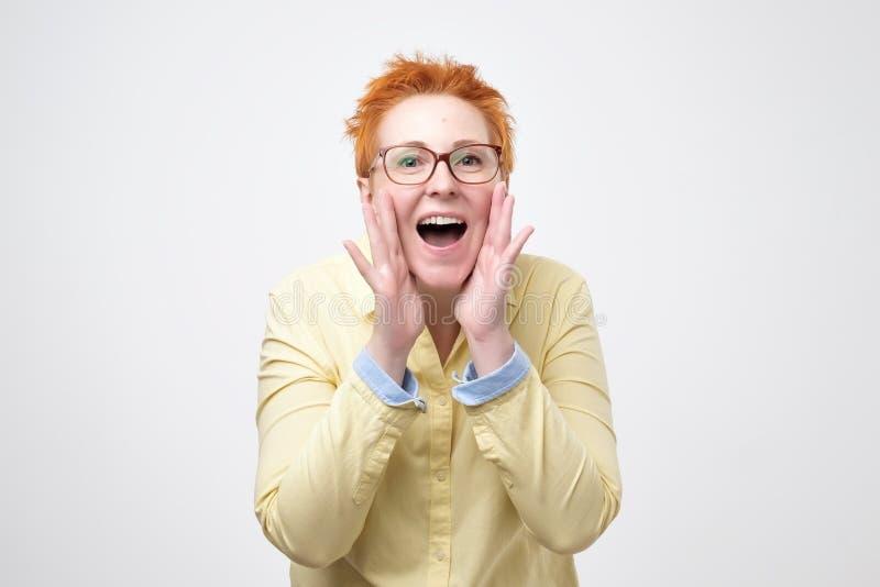 Sagen Sie niemandem Konzept Gesprächige prettyeuropean Frau mit dem roten Haar sagt geheime heiße bremsende Nachrichten stockbild