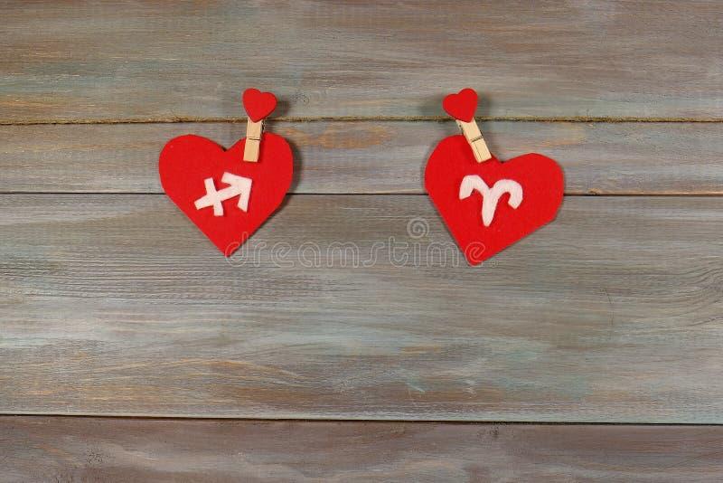 Sagitario y aries muestras del zodiaco y del corazón CCB de madera foto de archivo