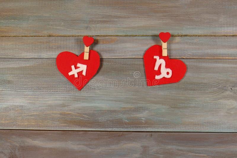 Sagitario y Capricornio muestras del zodiaco y del corazón De madera imagen de archivo libre de regalías