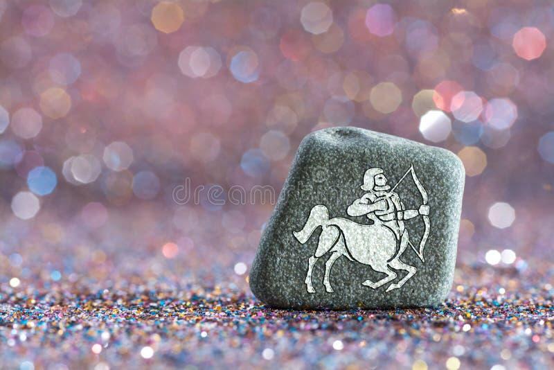 Sagittarius zodiac sign. A green stone with Sagittarius zodiac sign on glitter boke light background stock photography