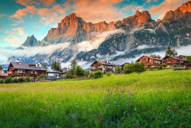 Sagolik bergsemesterort i dolomitesna, de färgrika vårblommorna med höga dimmiga berg och de gulliga trähusen på solnedgången, Sa arkivfoto