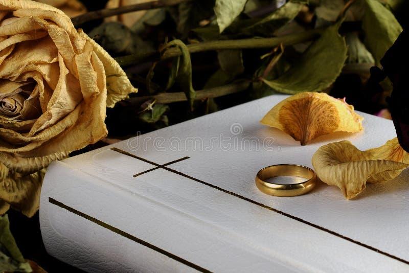 Sagrada Biblia blanca, un anillo de bodas y rosa seca del amarillo imagen de archivo