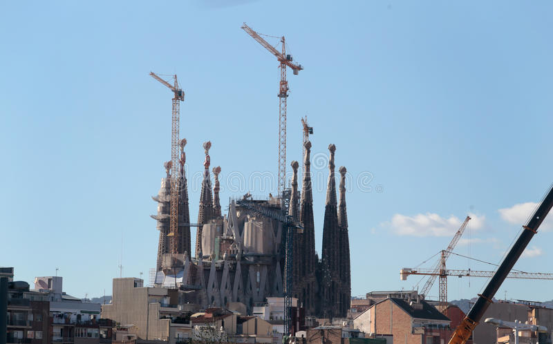 Sagrada familia cathedral over barcelona skyline. The Sagrada Familia cathedral and construction cranes over barcelona residentials skyline. Designed by royalty free stock photos