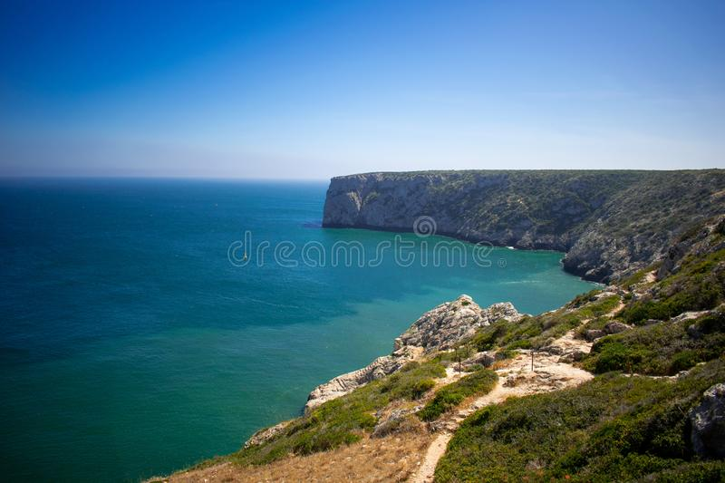 Sagres, Algarve Portugal High cliffs on coast of Atlantic Ocean near to lighthouse against blue sky royalty free stock images