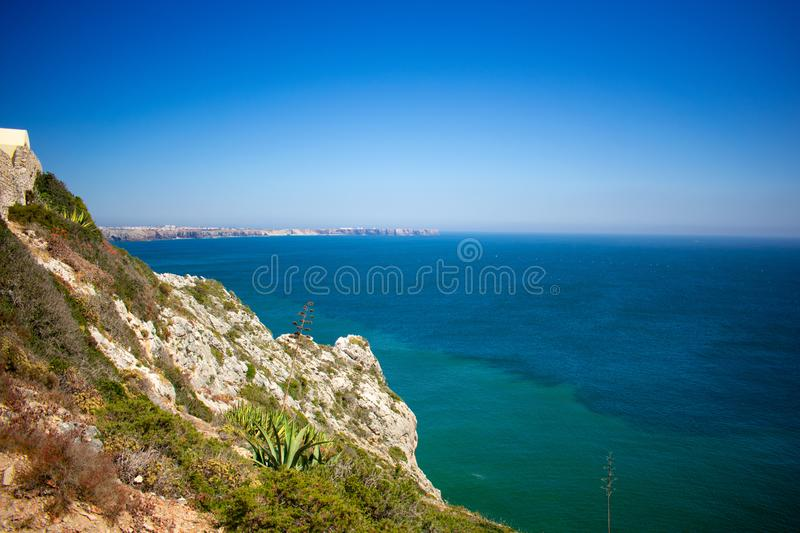 Sagres, Algarve Portugal High cliffs on coast of Atlantic Ocean near to lighthouse against blue sky stock images