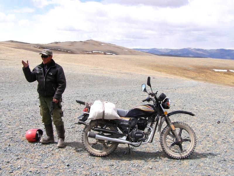 SAGSAY, MONGOLIË - MEI 22, 2012: Portretinwoner van de Mongoolse mens die maaltijd op zijn motorfiets aan huis in woestijnberg d stock foto's