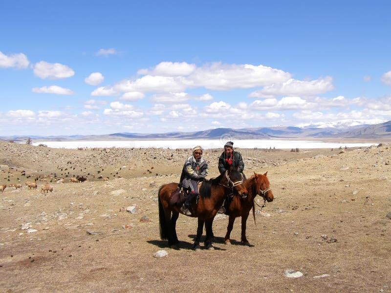 SAGSAY, MONGOLIA - MAY 22, 2012: Mongolian teenagers horsemen shepherd their sheep in the beautiful spring desert stock images