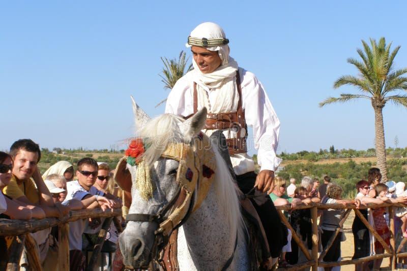 SAHARA TUNISIEN - JUNI 2008: Arabiska nomader på hästrygg i nationell dräkt royaltyfria bilder