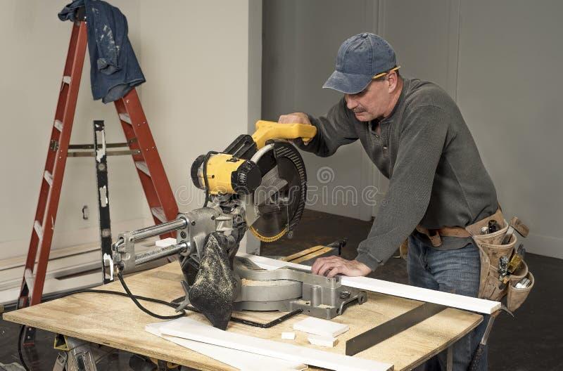 Sahen tragender Werkzeuggurt des männlichen Tischlers und der Schnitt des hölzernen Brettes mit Berufshieb auf Baustellehaus umge lizenzfreie stockfotos