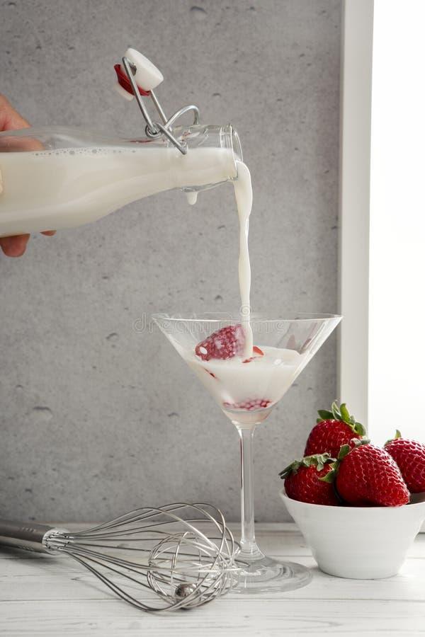 Sahnen Sie über Erdbeeren in Martini-Glas gegossen werden lizenzfreies stockbild