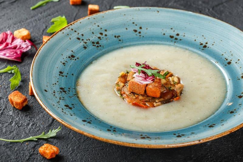 Sahnesuppe des Selleries mit tartare vom gebackenen Gem?se verziert von den Croutons und vom Arugula in der Platte auf dunklem St lizenzfreie stockbilder