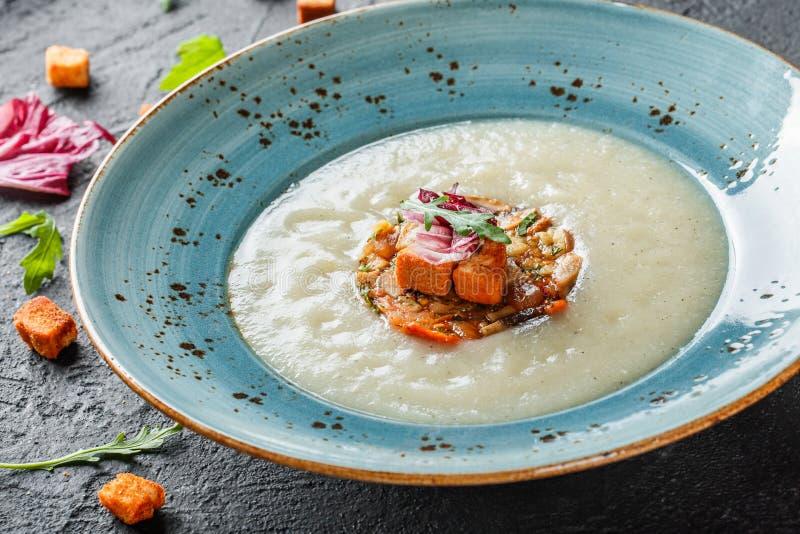 Sahnesuppe des Selleries mit tartare vom gebackenen Gem?se verziert von den Croutons und vom Arugula in der Platte auf dunklem St stockfotos