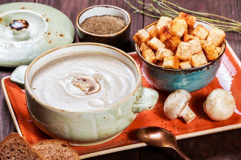 Sahnesuppe mit Pilzen, Kräutern, Creme und Crackern auf Platte auf dunklem hölzernem Hintergrund Selbst gemachte Nahrung lizenzfreies stockfoto