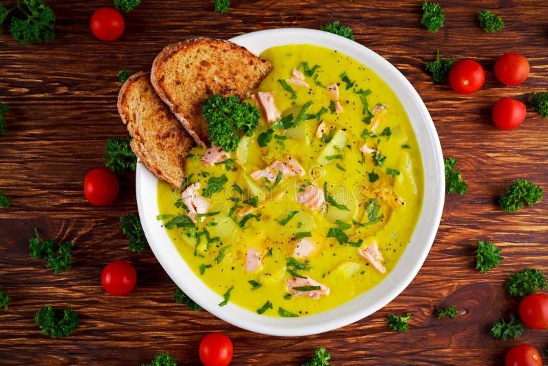 Sahnige Fische Lachse, Porree, Kartoffelsuppe auf hölzernem Hintergrund lizenzfreie stockfotografie