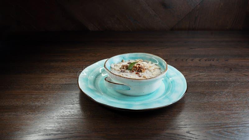 Sahnige Sahnegemüsesuppe von Pilzen mit Walnüssen und Kürbiskernen auf dem Tisch in einem Restaurant, das orientalische Küche die lizenzfreies stockbild