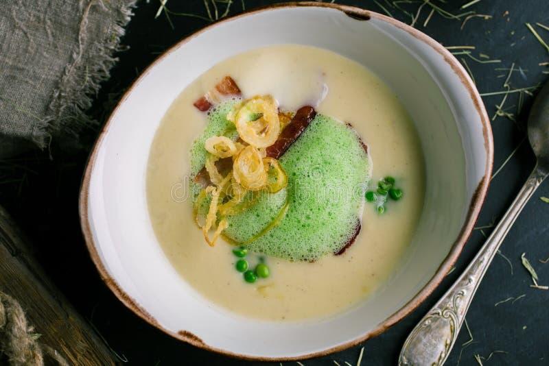 Sahnige Suppe mit Speck und grünen Erbsen vom Chef lizenzfreie stockbilder