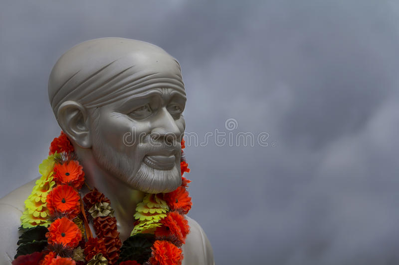 Sai Baba face. In a grey sky background stock images