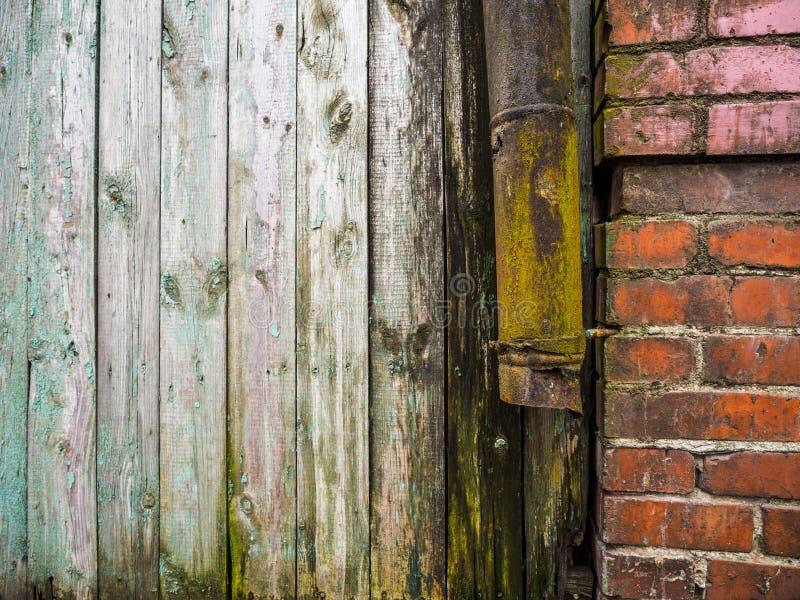 Saia a água da chuva do telhado de uma construção na chuva Drenagem oxidada velha da água da chuva imagem de stock