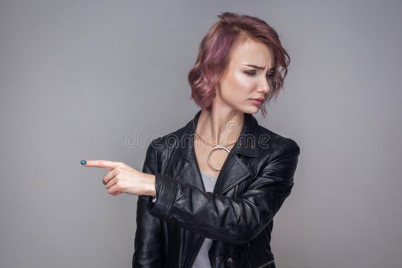 Saia de aqui Retrato da mulher descontentada com cabelo curto e da composição na posição preta do casaco de cabedal do estilo oca fotos de stock royalty free