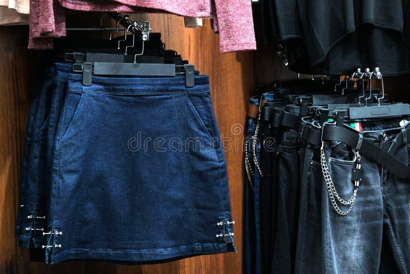 Saia e calças da sarja de Nimes na loja dos ganchos Conceito para o projeto e vendas de compra Roupa moderna da forma das mulhere imagens de stock royalty free