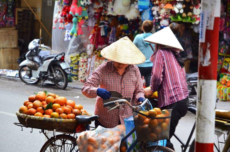 SAIGION, ВЬЕТНАМ 6-ое марта: Уличный торговец женщины продавая большой оранжевый плодоовощ в Вьетнаме стоковые изображения rf