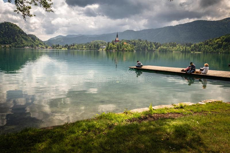 Saigné, la Slovénie - 18 mai 2019 : les gens appréciant la belle vue sur le lac saigné, s'asseyant et se trouvant sur la passerel photographie stock