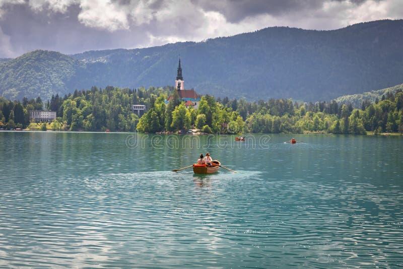 Saigné, la Slovénie - 18 mai 2019 : Touristes heureux ramant dans le bateau plat en bois ayant l'amusement sur le lac saigné en c photos stock
