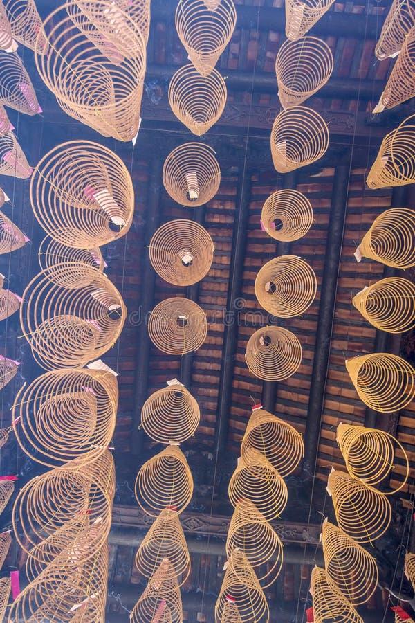 SAIGON, VIETNAM - 13 de febrero de 2018 - incienso espiral pega la ejecución del techo en la pagoda de Thien Hau, dedicada al mar fotos de archivo