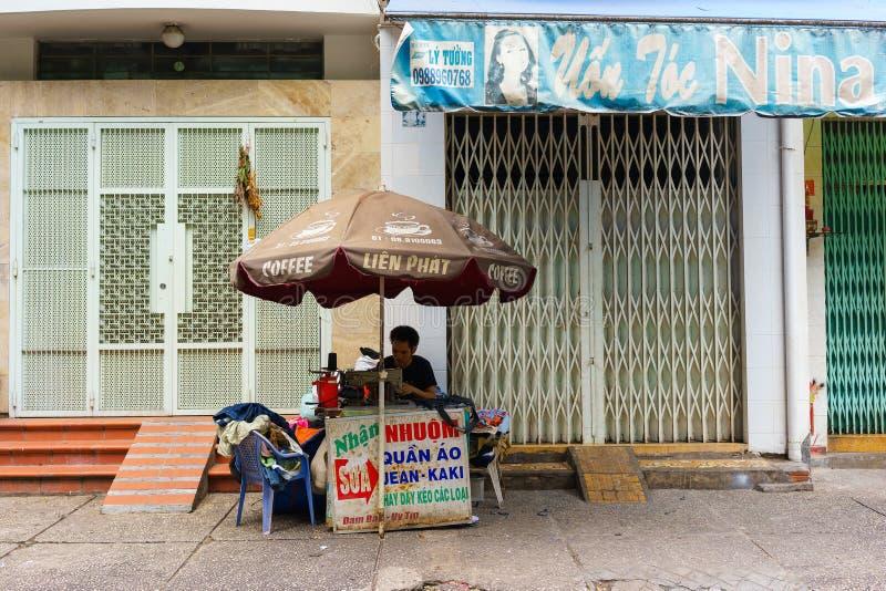 SAIGON VIETNAM - Oktober 16, 2014: En fixande beklär mannen på en liten gata, Saigon, Vietnam royaltyfria foton