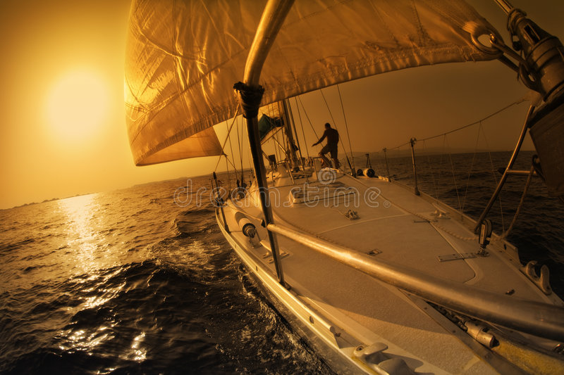 Sail boat. People on a sail boat at the sunset